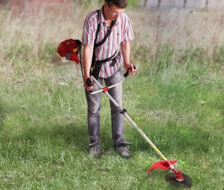 Mann mit Freischneider im Garten