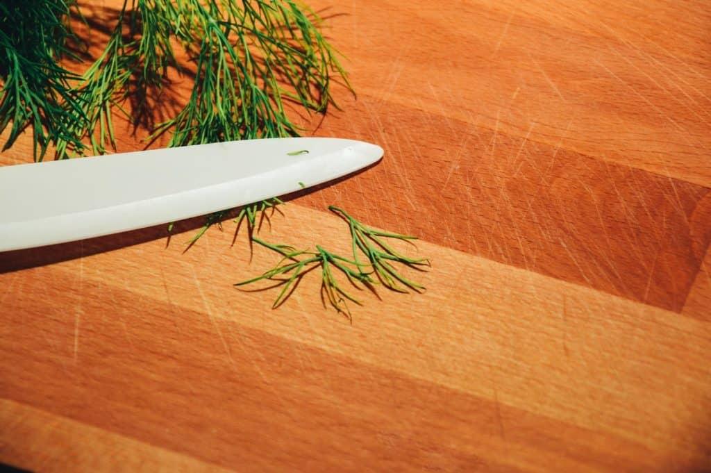 Dill mit Messer auf Holzbrett