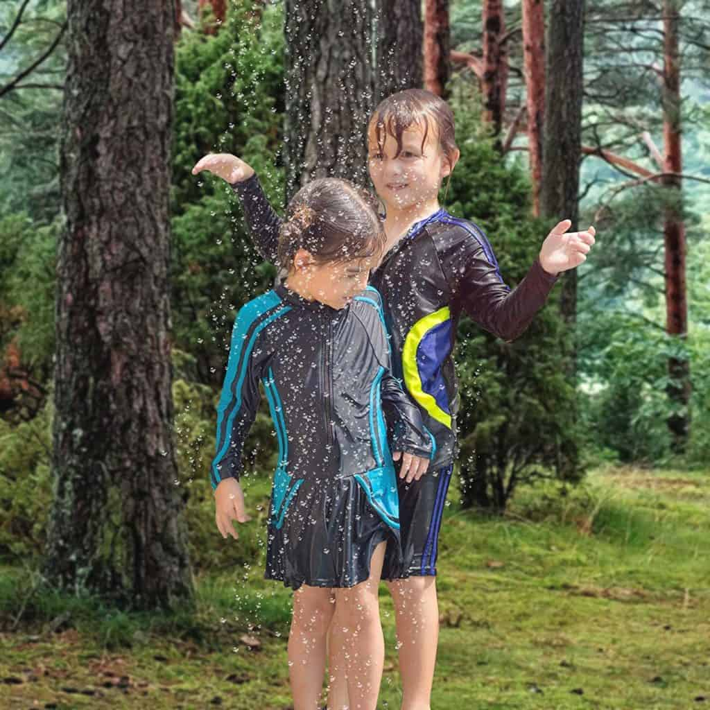 Kinder unter einer Dusche im Garten